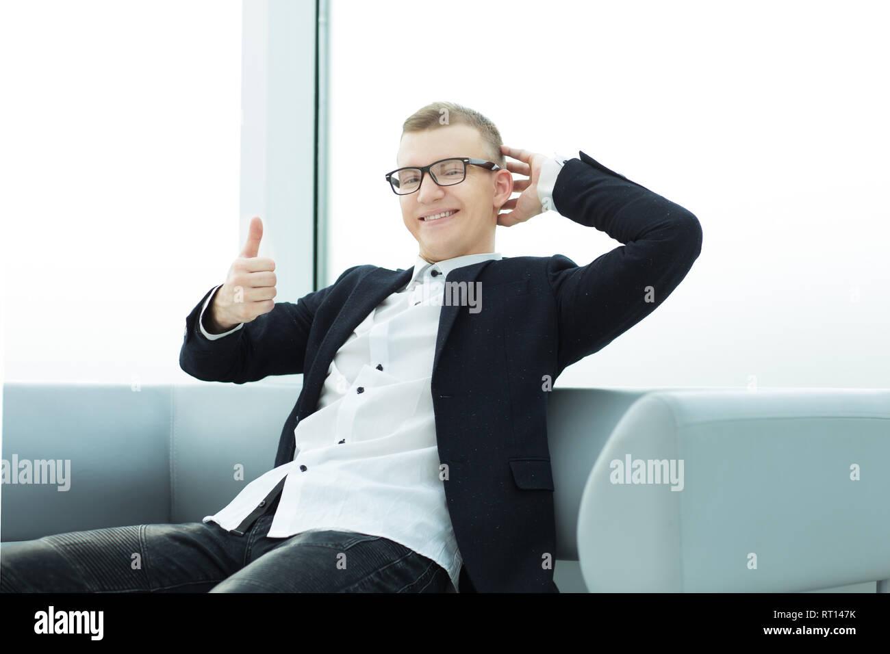 Empresario sentado en el vestíbulo del centro de negocios y mostrando el pulgar hacia arriba. Imagen De Stock