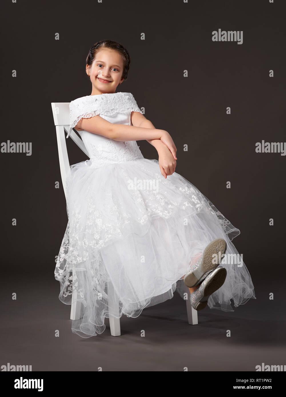 8878213d0 Niña vestida de un vestido blanco y sentado en la silla