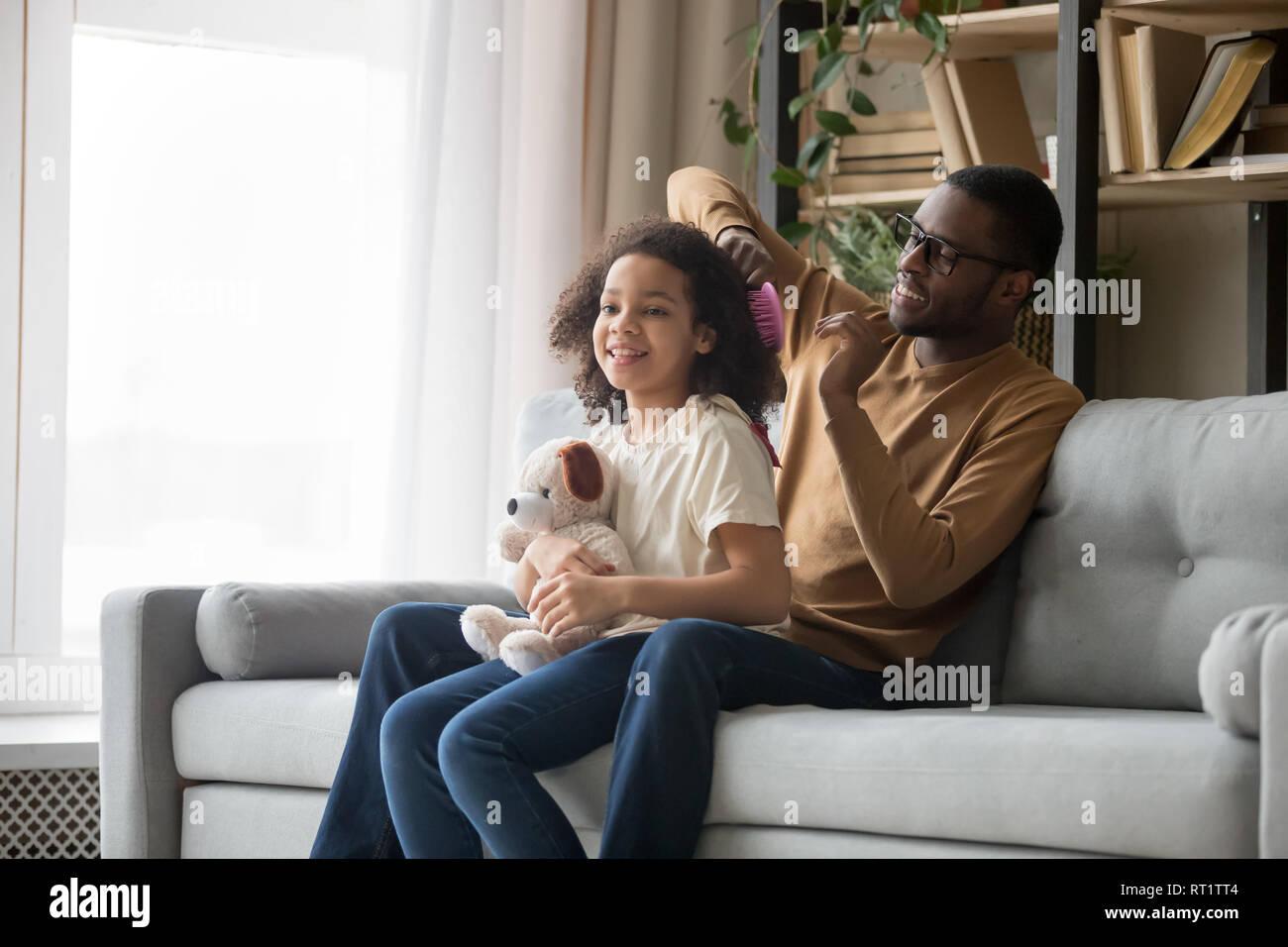 Papá africano cepillarse el cabello haciendo de hija sentada en un sofá Foto de stock