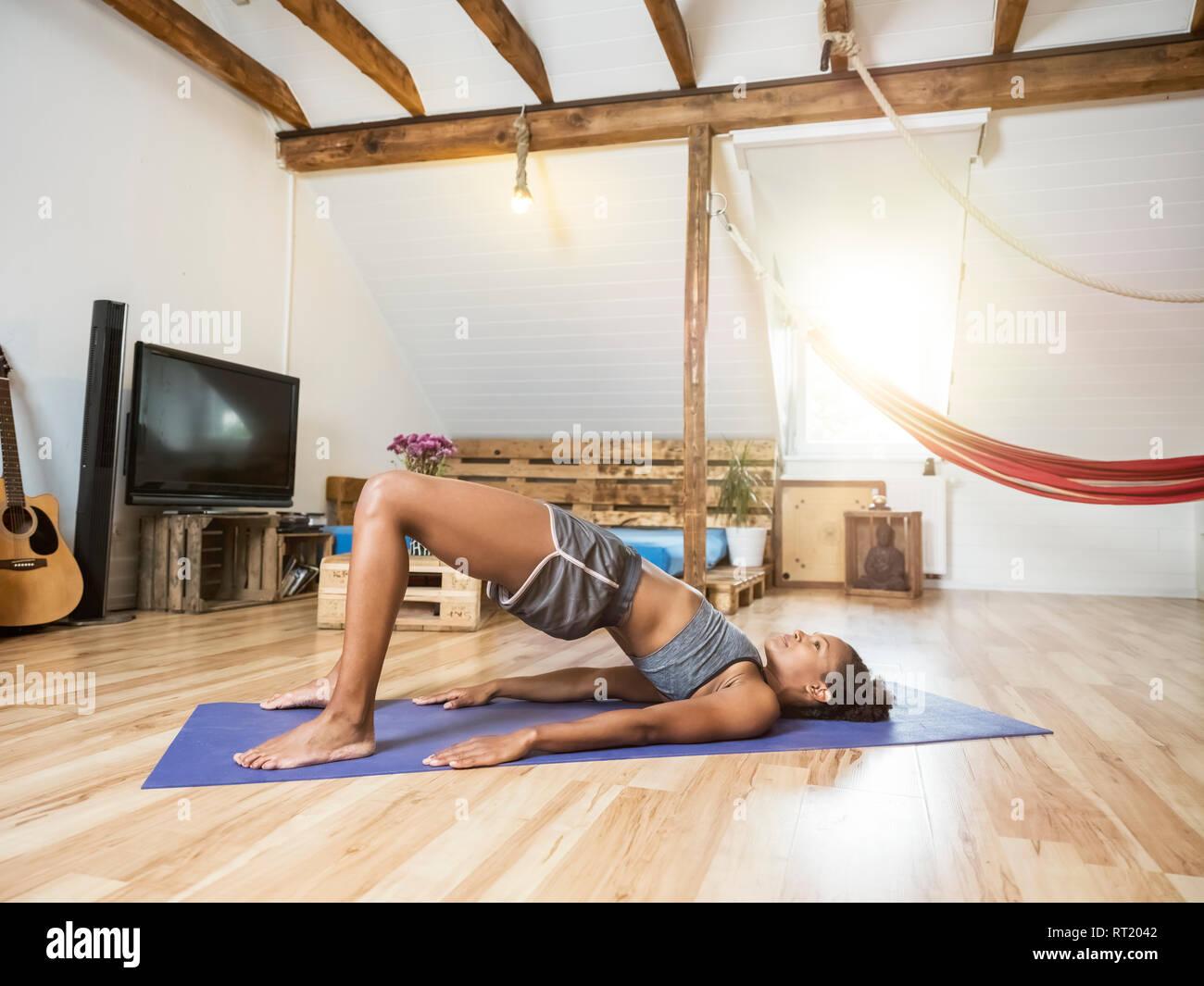 Mujer joven practicando yoga en buhardilla Imagen De Stock