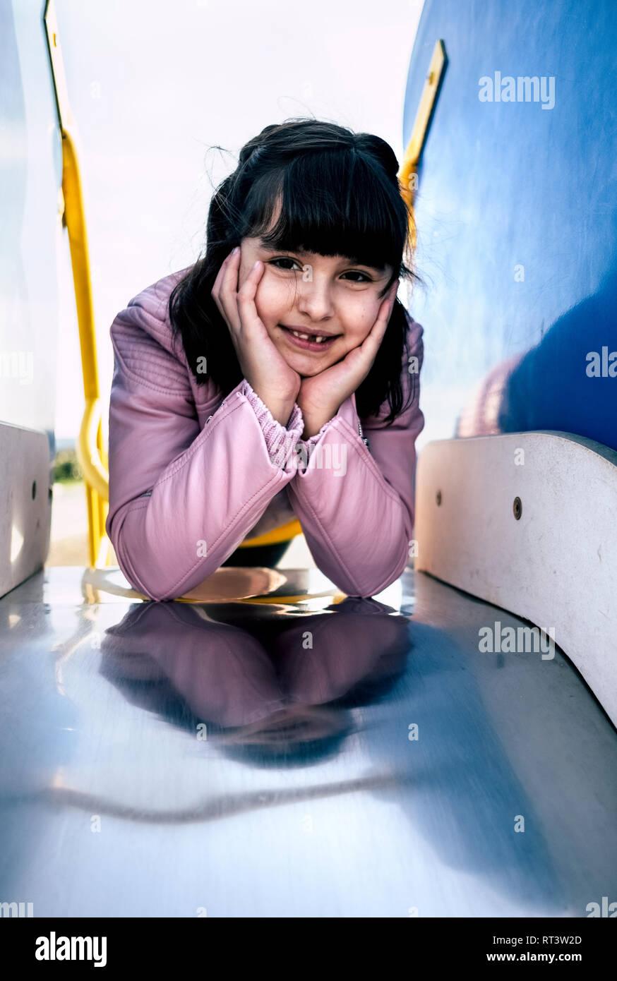 Retrato de muchacha recostada en la diapositiva de un playground Imagen De Stock