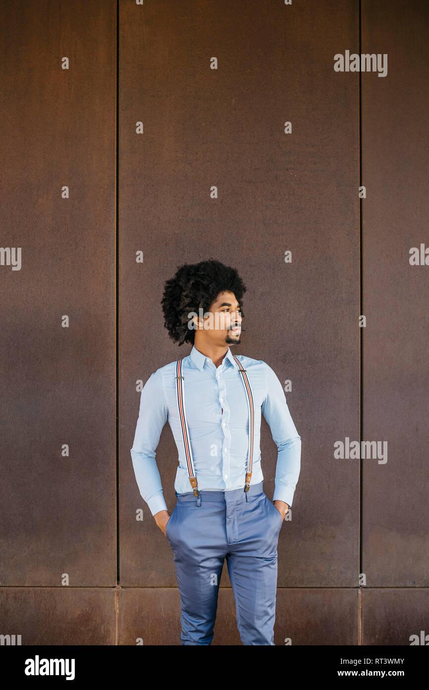 Barbado hombre vestido con camisa y tirantes de pie delante de rusty antecedentes Foto de stock