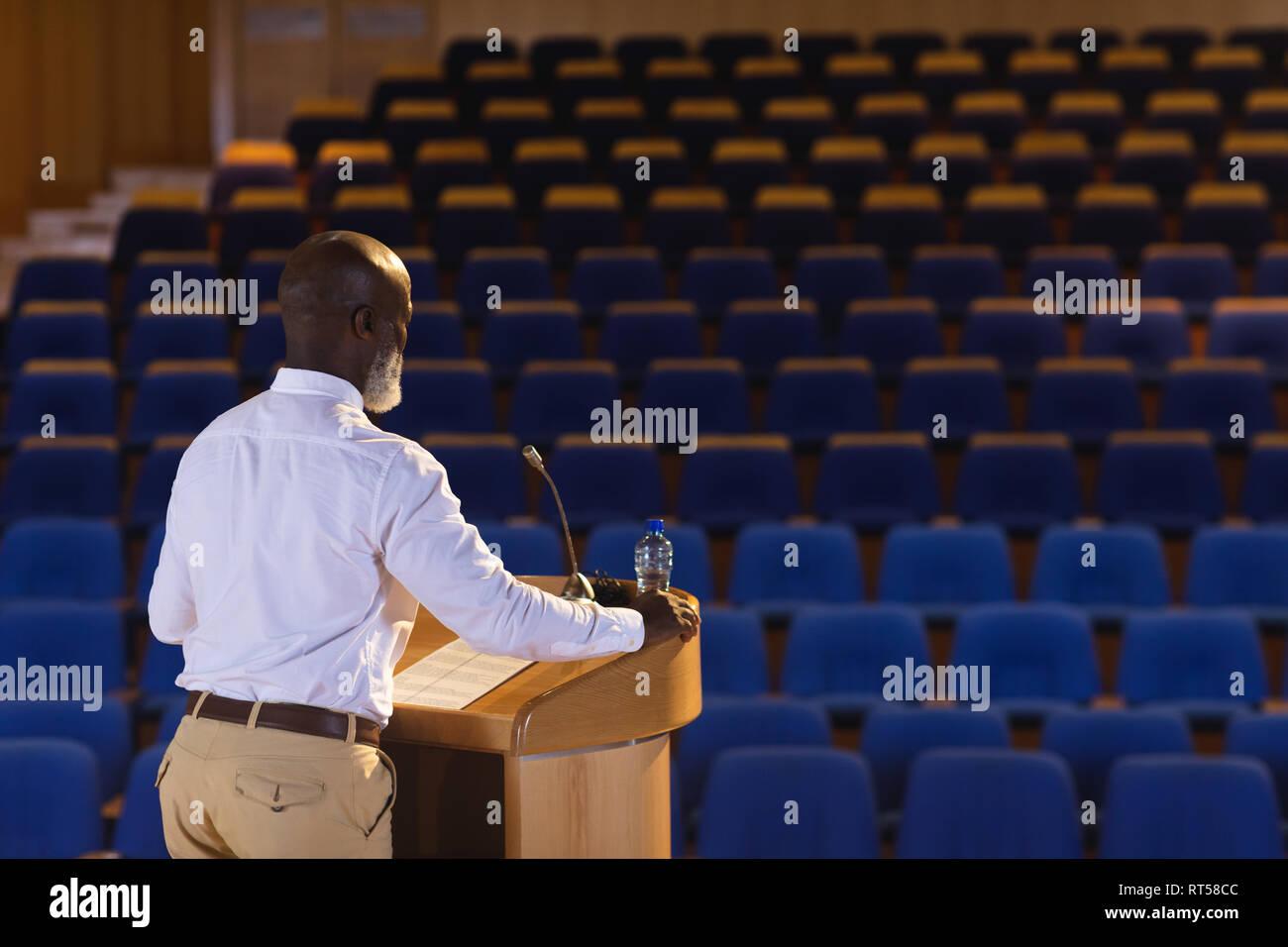 Madurado empresario practicando por el discurso en el auditorio vacío Imagen De Stock