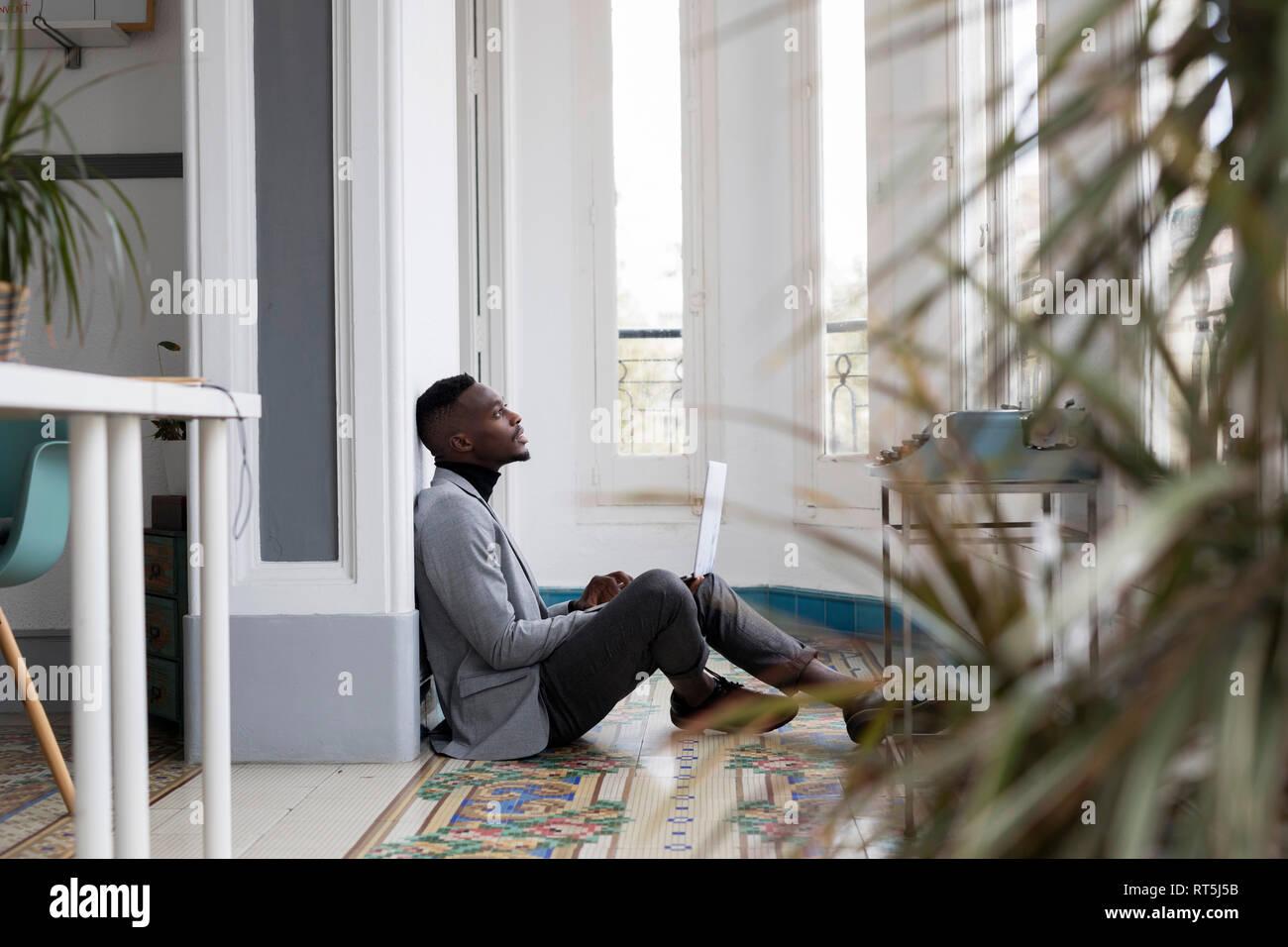 Empresario joven sentada en el suelo en la oficina con un portátil pensando Foto de stock