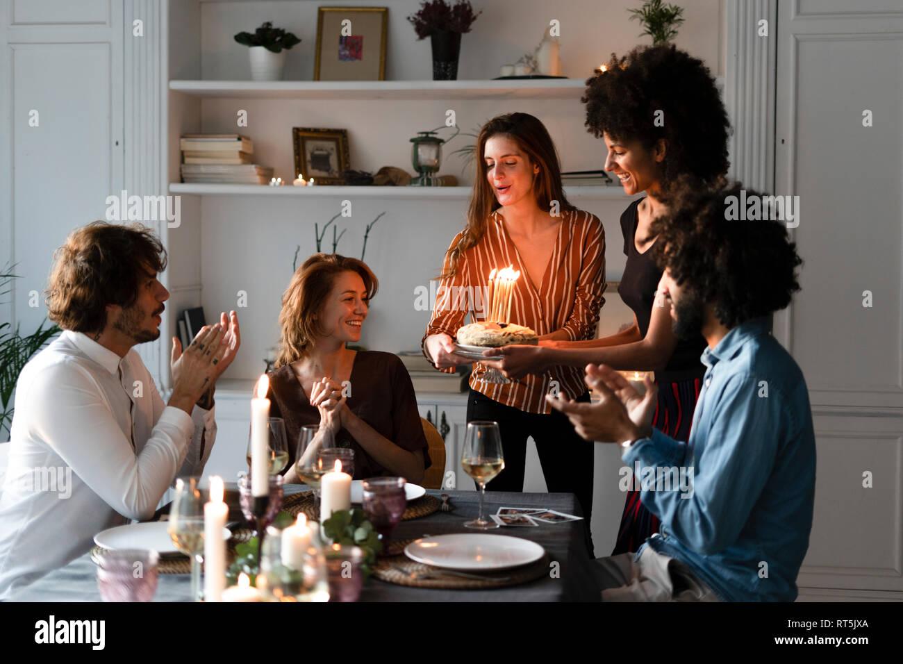 Amigos sorprendente joven con una tarta de cumpleaños con velas encendidas Imagen De Stock