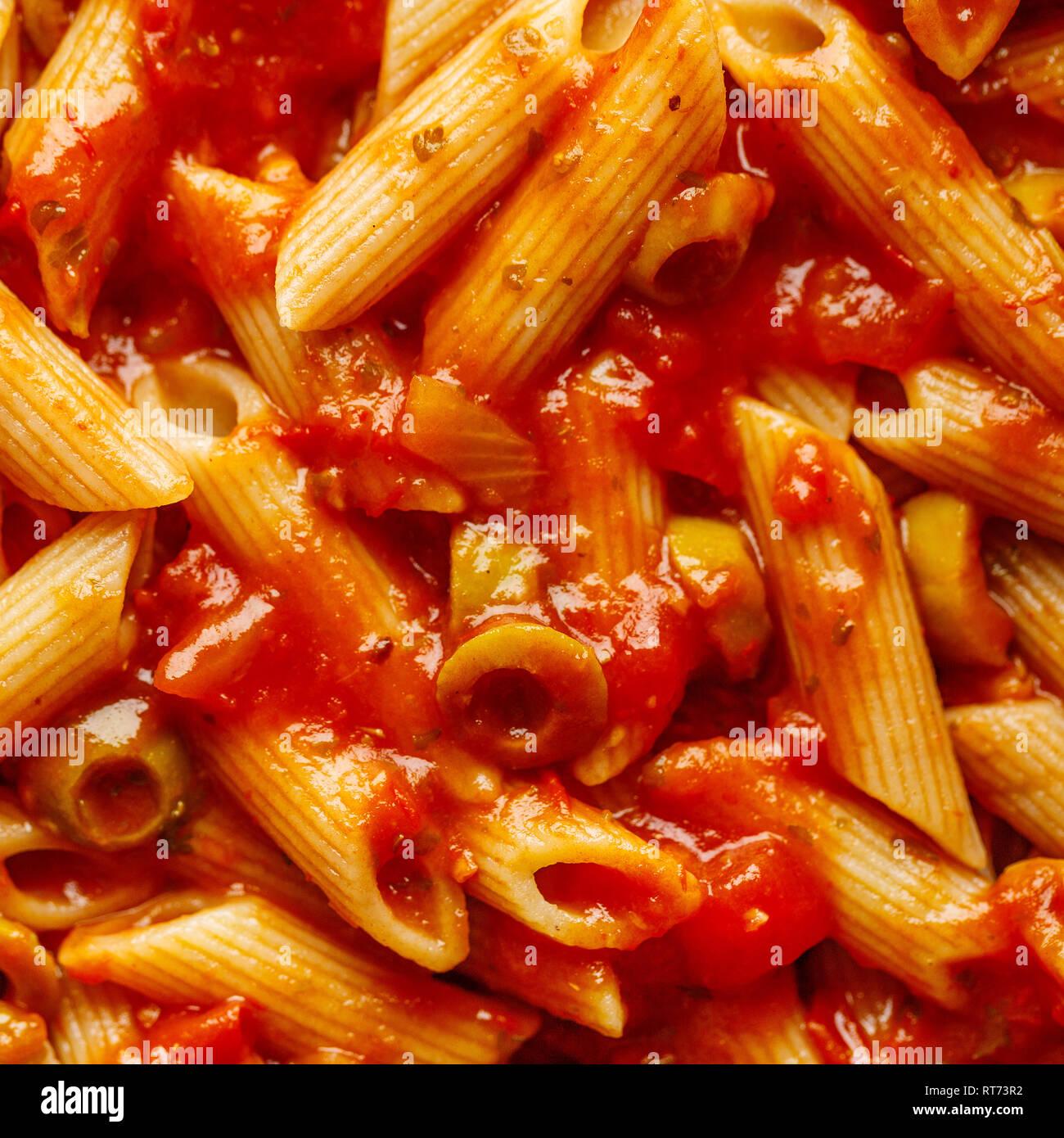 Primer plano de una sabrosa sabrosa pasta penne con salsa de tomate y aceitunas. Macro shot. Fondo oscuro. Closeup. Foto de stock