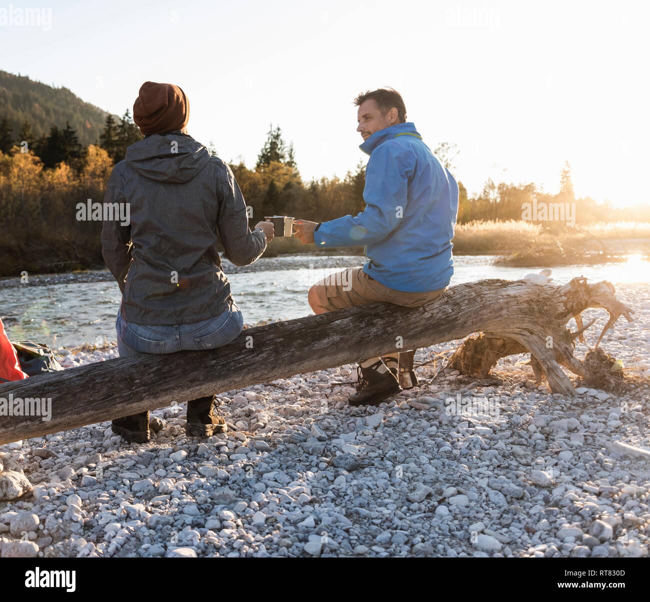 Pareja camping en Riverside en la luz de la tarde Foto de stock