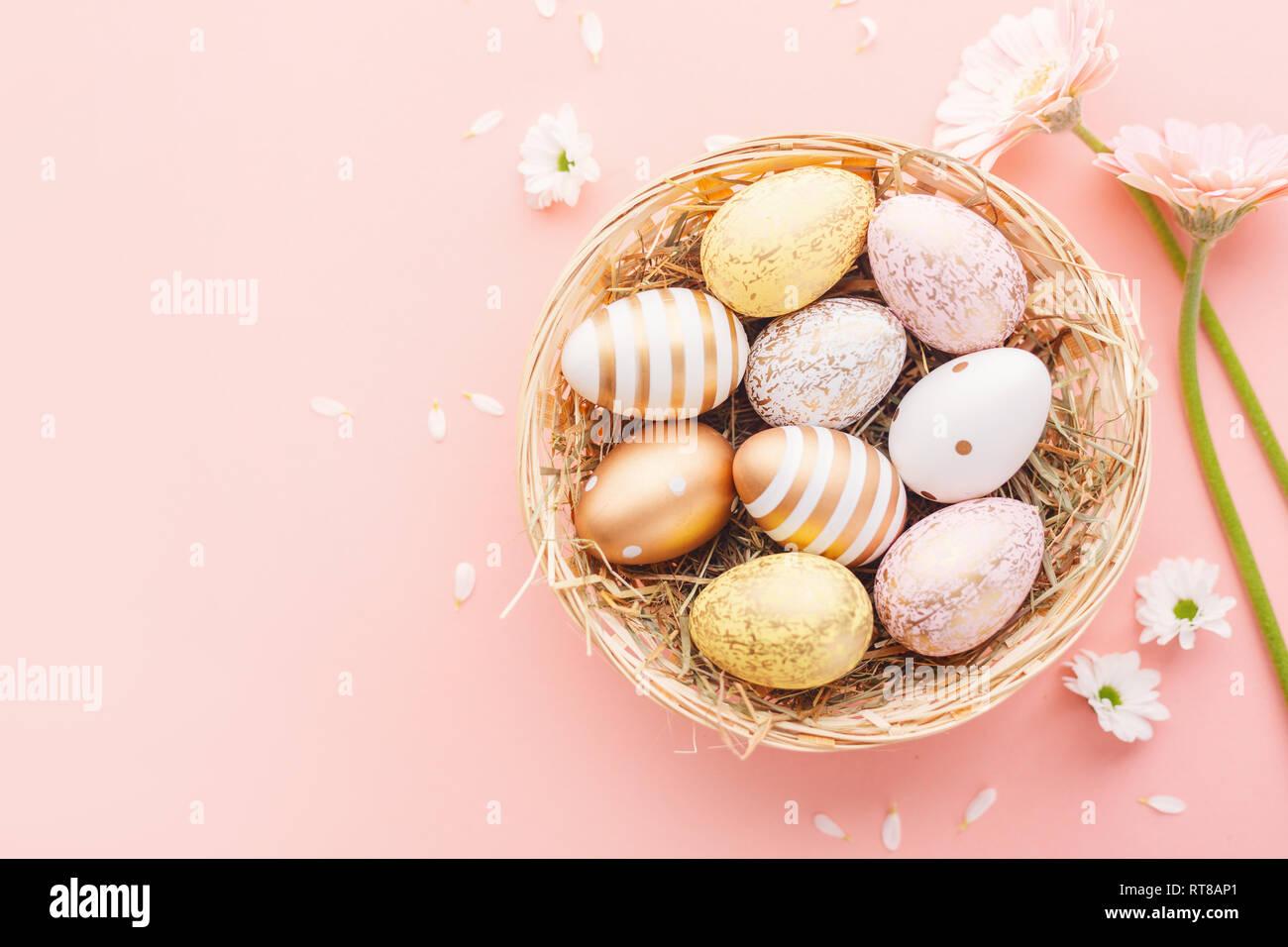 Sentar planas de huevos de Pascua el patrón oro con pequeñas flores y pétalos de color rosa de fondo. Pascua Pascua de fondo o concepto. Horizontal. Foto de stock