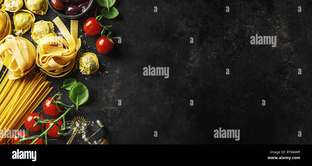 Fondo de alimentos. Antecedentes La comida italiana con pastas, ravioles, tomate, aceitunas y albahaca sobre un fondo oscuro. Horizontal con espacio de copia. Foto de stock