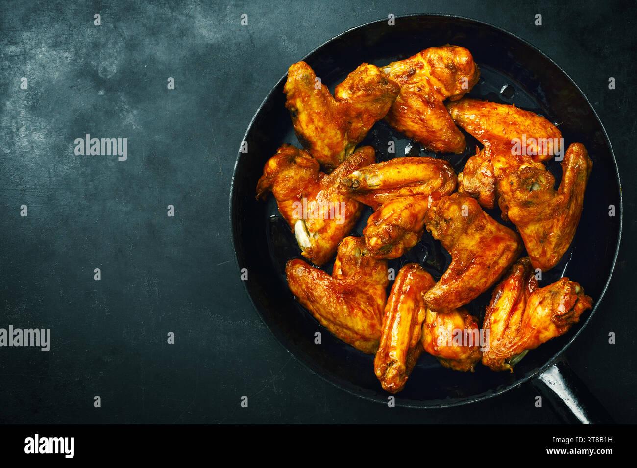 Sabrosas alitas de pollo al horno o a la parrilla servido en salsa de pan. Fondo oscuro. Horizontal. Foto de stock