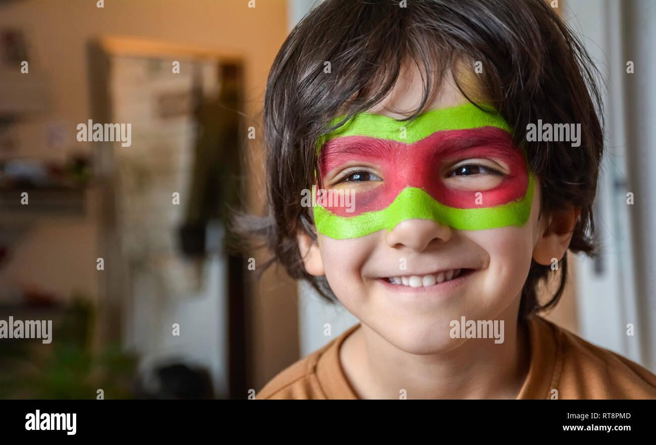 Retrato de niño sonriente con pintura de cara - Cara de Niño pintado sobre fondo borroso Foto de stock
