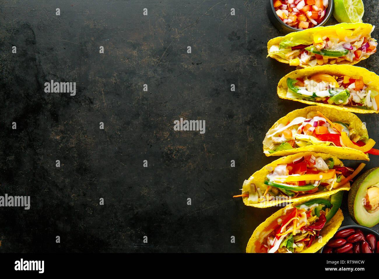 Sabroso apetitosos tacos con pollo, verduras y salsa servido sobre fondo oscuro. Vista superior con espacio de copia. Horizontal. Foto de stock