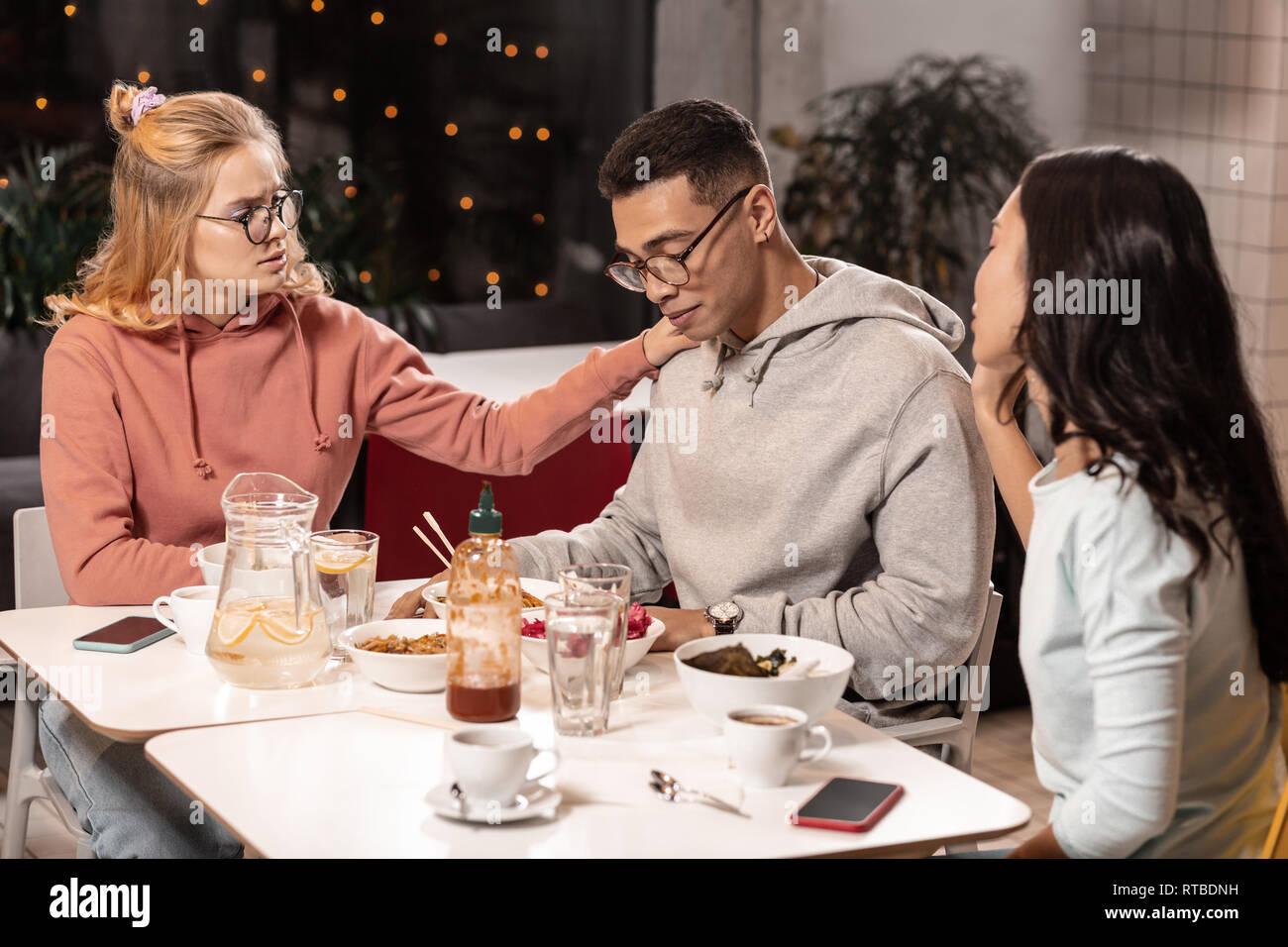 Adorables chicas intentando consolar a Guy haciendo fotos con él. Imagen De Stock