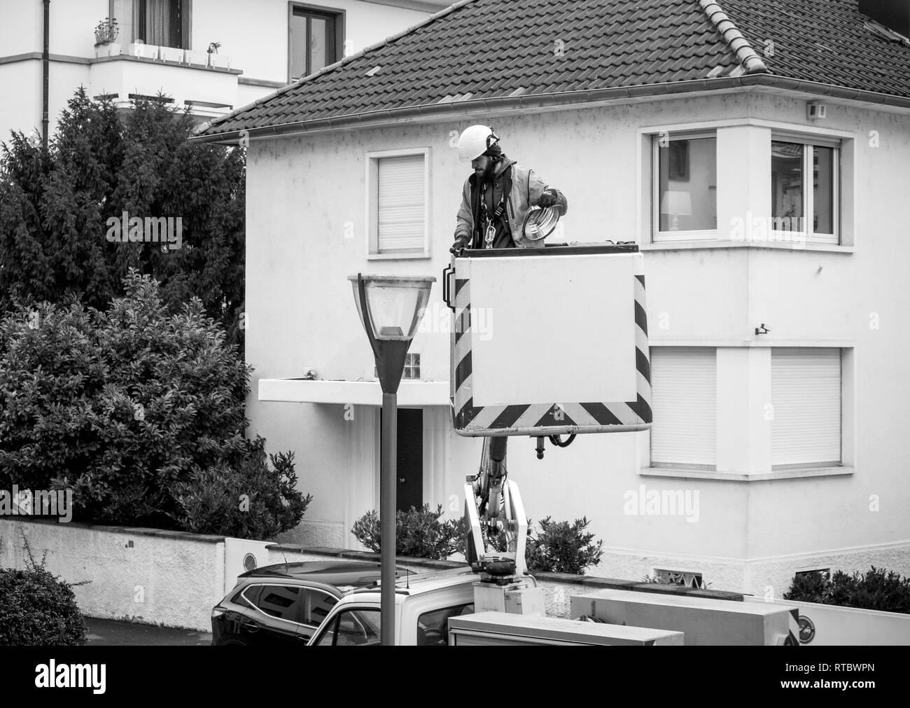 París, Francia - DEC 16, 2017: limpieza trabajador reparar cambiando el tubo luminoso de un mástil ligero en París por la noche, la seguridad y la protección en el barrio Foto de stock
