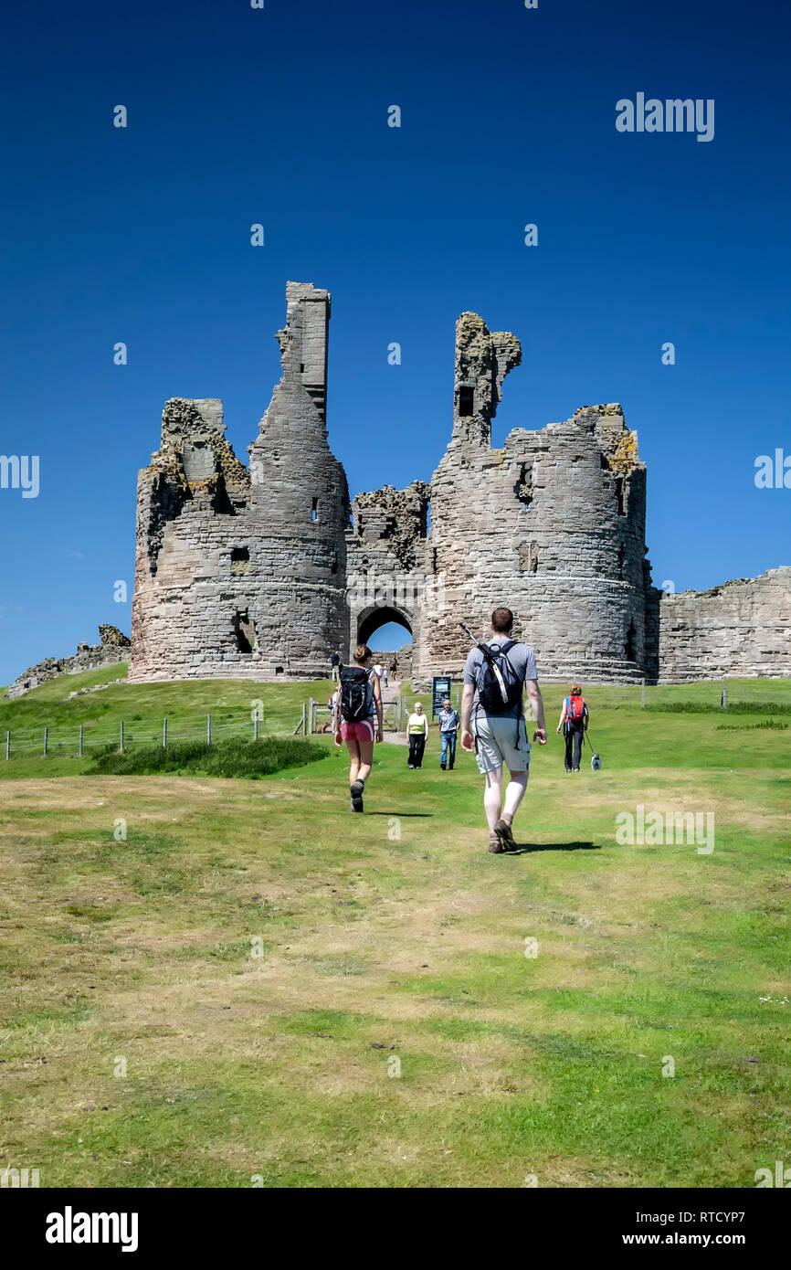 Los excursionistas en el castillo de Dunstanburgh, England, Reino Unido Foto de stock