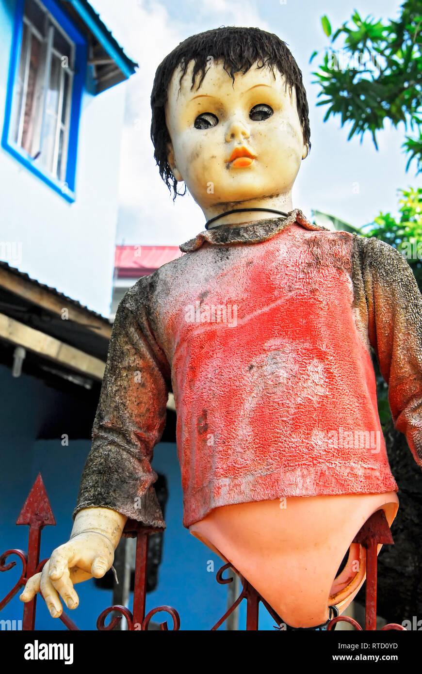 Una muñeca de plástico colorido sucio sin piernas atrapadas en un jardín vallado. Es una vista de ángulo bajo con una casa en el fondo, visto en Filipinas Foto de stock