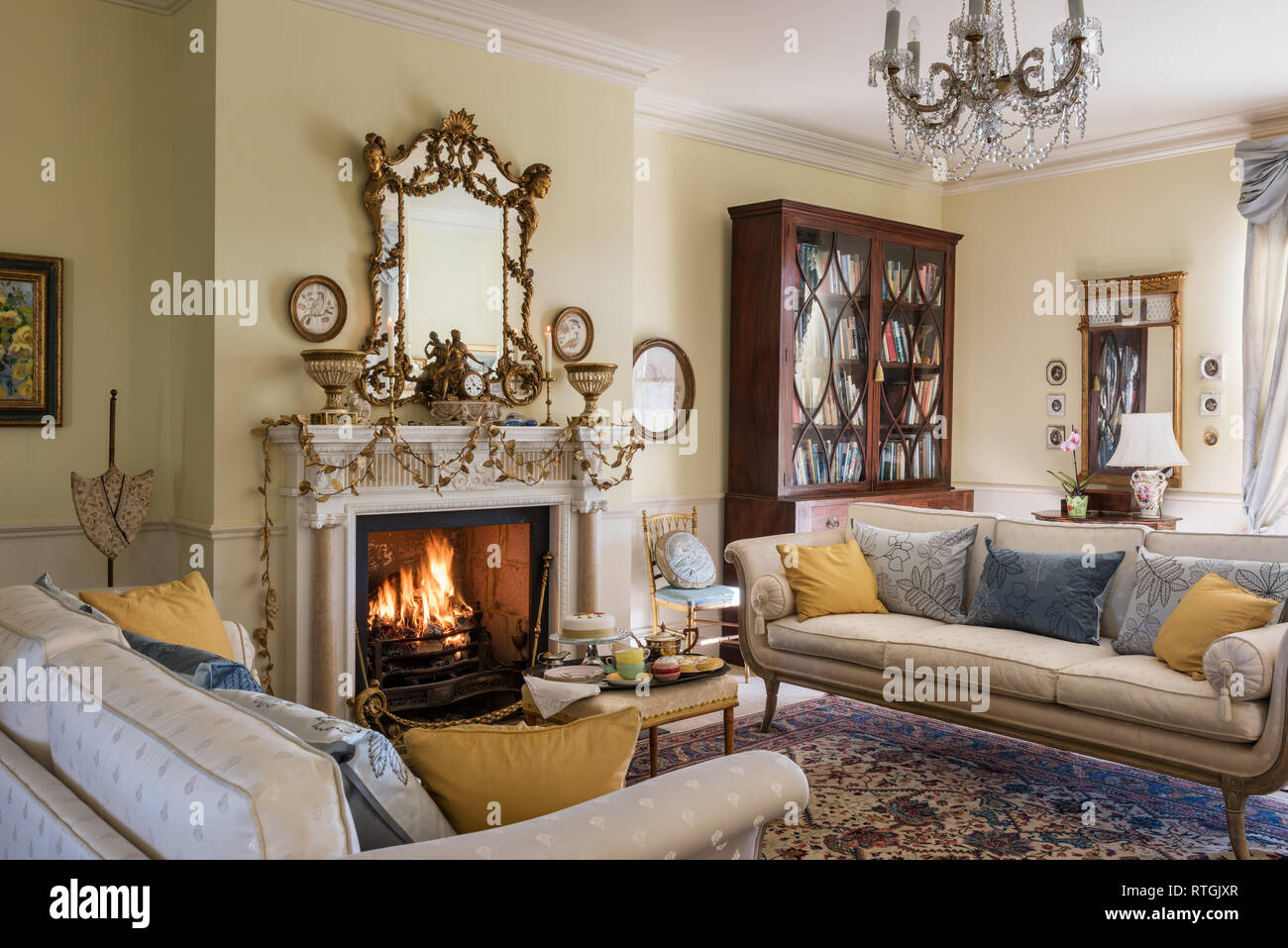 Alfombras orientales con sofás de estilo regencia y goldleaf garland en inglés chimenea Imagen De Stock