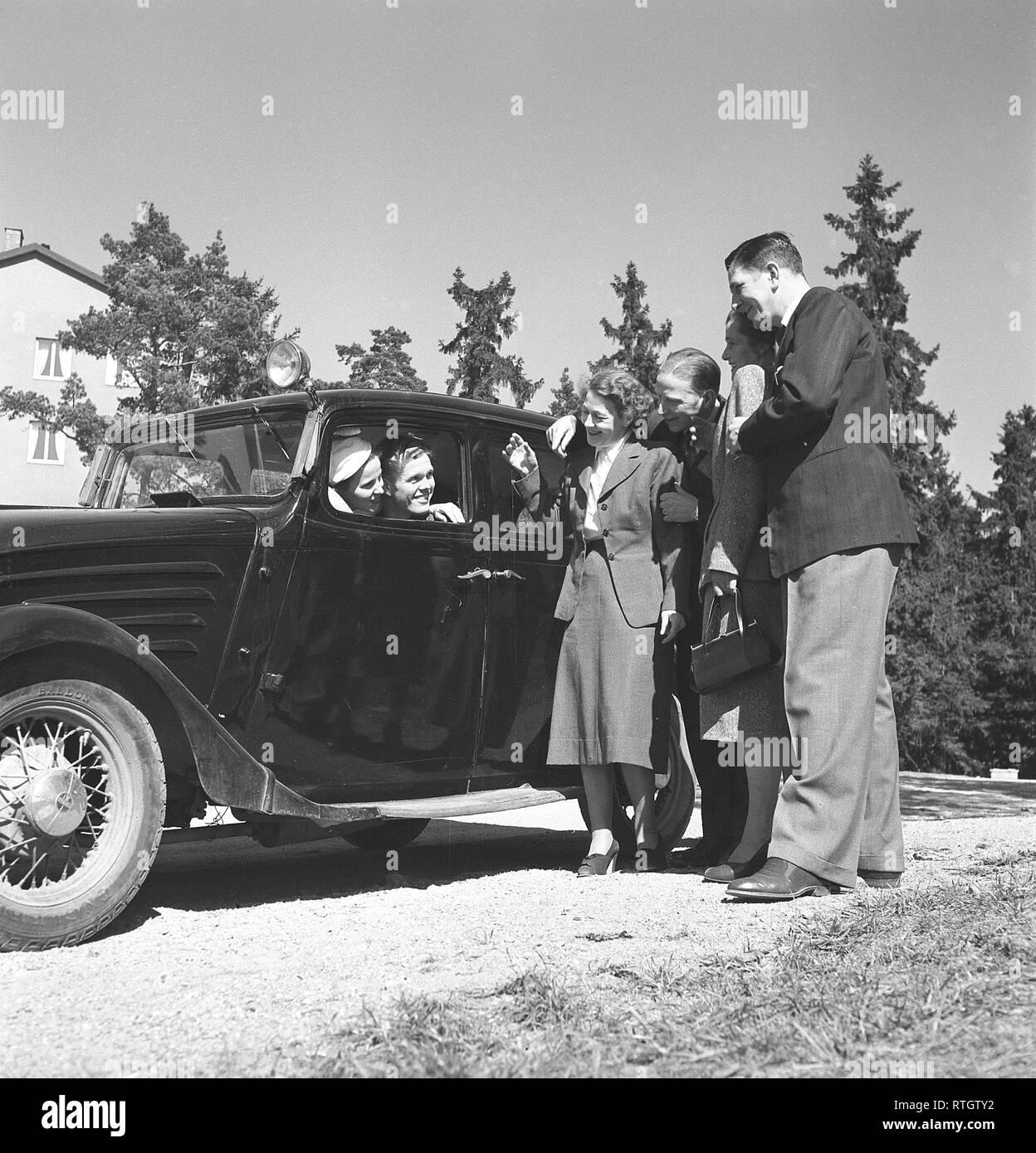 Estilo de vida en la década de 1950. Una pareja joven en su cámara diciendo adiós a un grupo de personas que han visitado. Foto Kristoffersson Ref BF77-2. Suecia 1952 Foto de stock