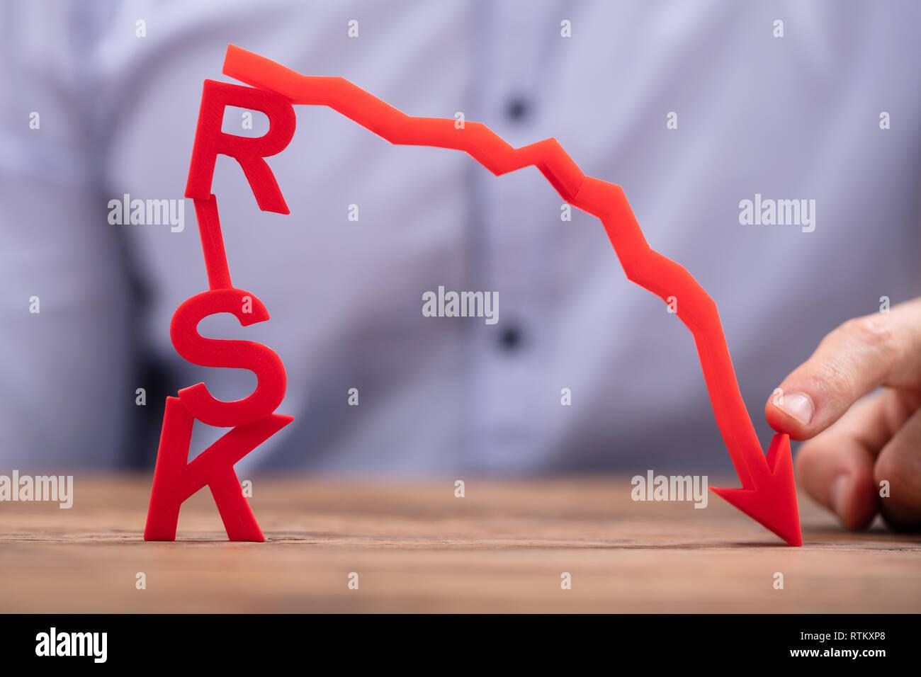 Empresario disminuyendo la flecha roja apuntando allí riesgo texto sobre un mostrador de madera Foto de stock