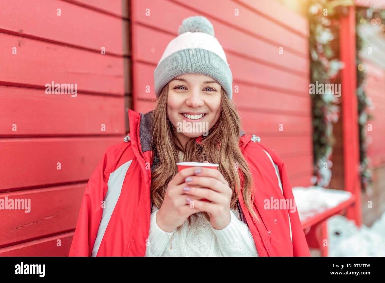 Bella mujer en invierno en una chaqueta sobre un fondo de color rojo con contraventanas de madera. Sosteniendo una taza de café, té. Feliz sonriendo y riendo. Holiday Resort Foto de stock