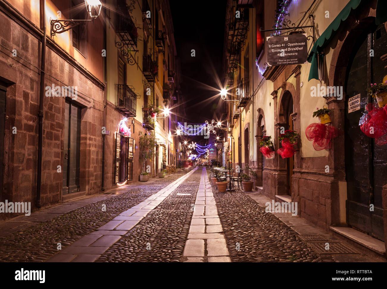 Bosa, isla Cerdeña Italia - 29 de diciembre de 2019: turista relajarse durante la noche en las antiguas calles de Bosa, Cerdeña, Italia Foto de stock