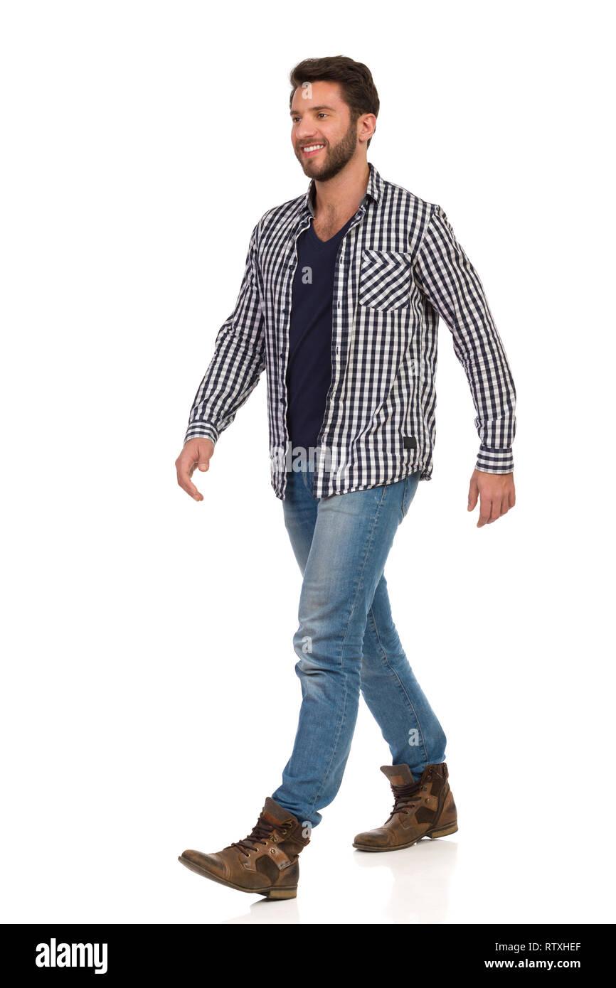 Hombre caminando con botas, pantalones vaqueros y camisa