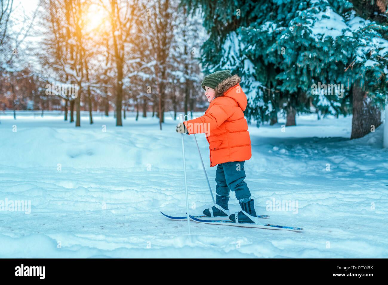 Un niño de 4-6 años en una chaqueta roja sobre esquís para niños. En invierno, en el parque de la ciudad, primeros pasos sobre los esquís, el comienzo de las actividades deportivas Foto de stock