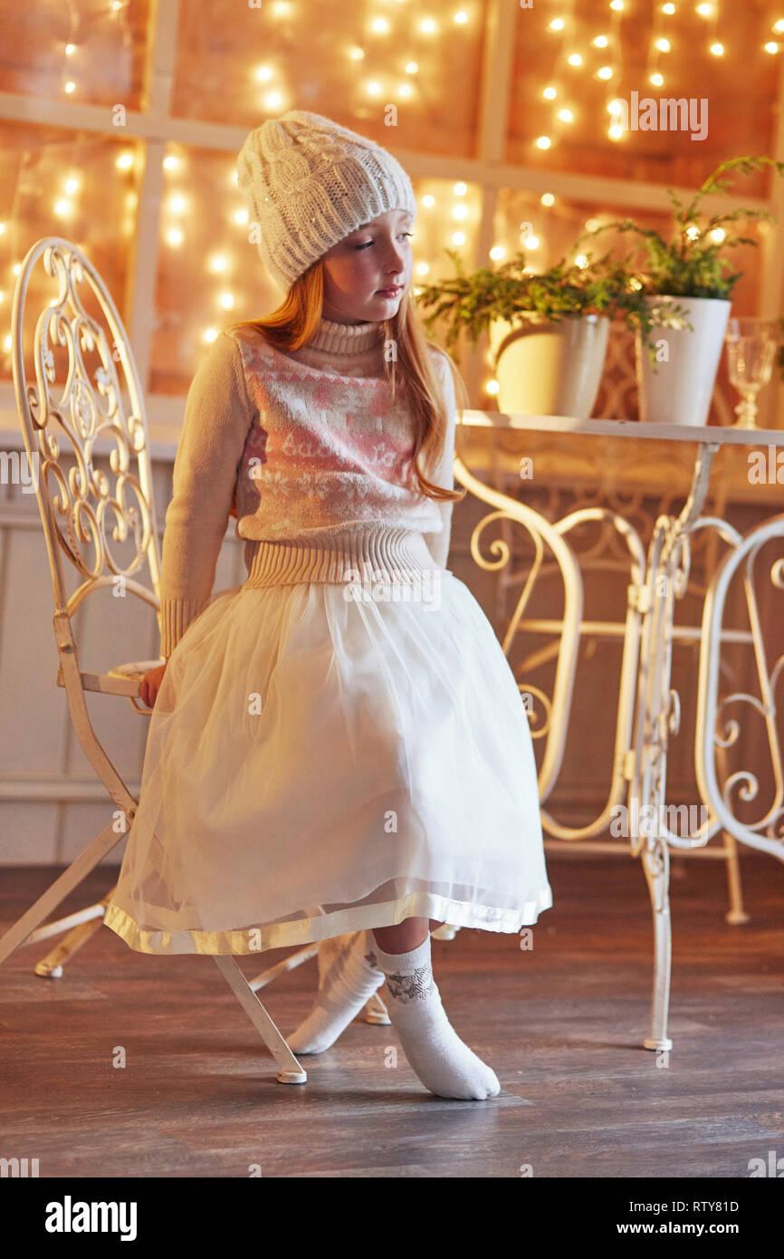 e91de838f Brillante niña pelirroja en un sombrero blanco y un hermoso vestido está  sentado en un café