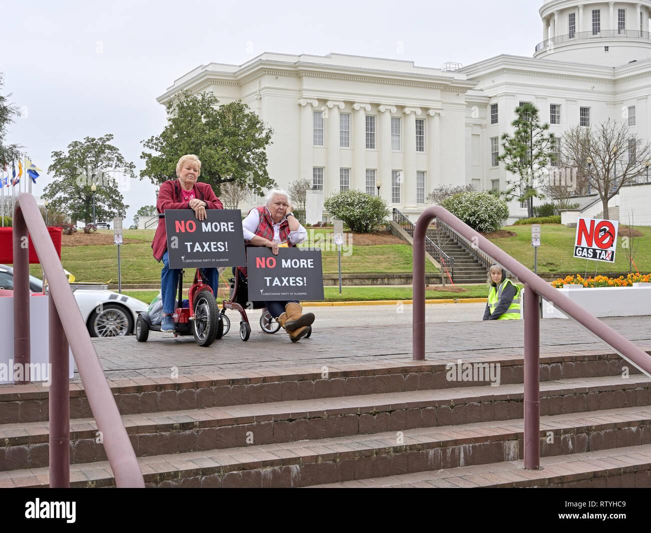 Dos ancianos o mujeres mayores en sillas de ruedas portando letreros de no más impuestos escuchar a un orador protestando por elevados impuestos a la gasolina en Alabama, Estados Unidos. Imagen De Stock