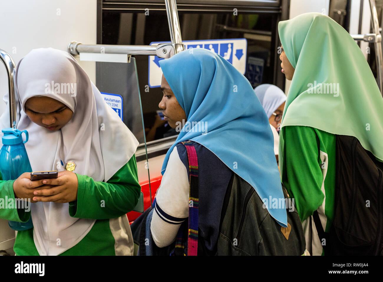 Las niñas en Malasia adolescente típica vestimenta musulmana moderada esperando a bordo de un autobús, Kuala Lumpur, Malasia. Foto de stock