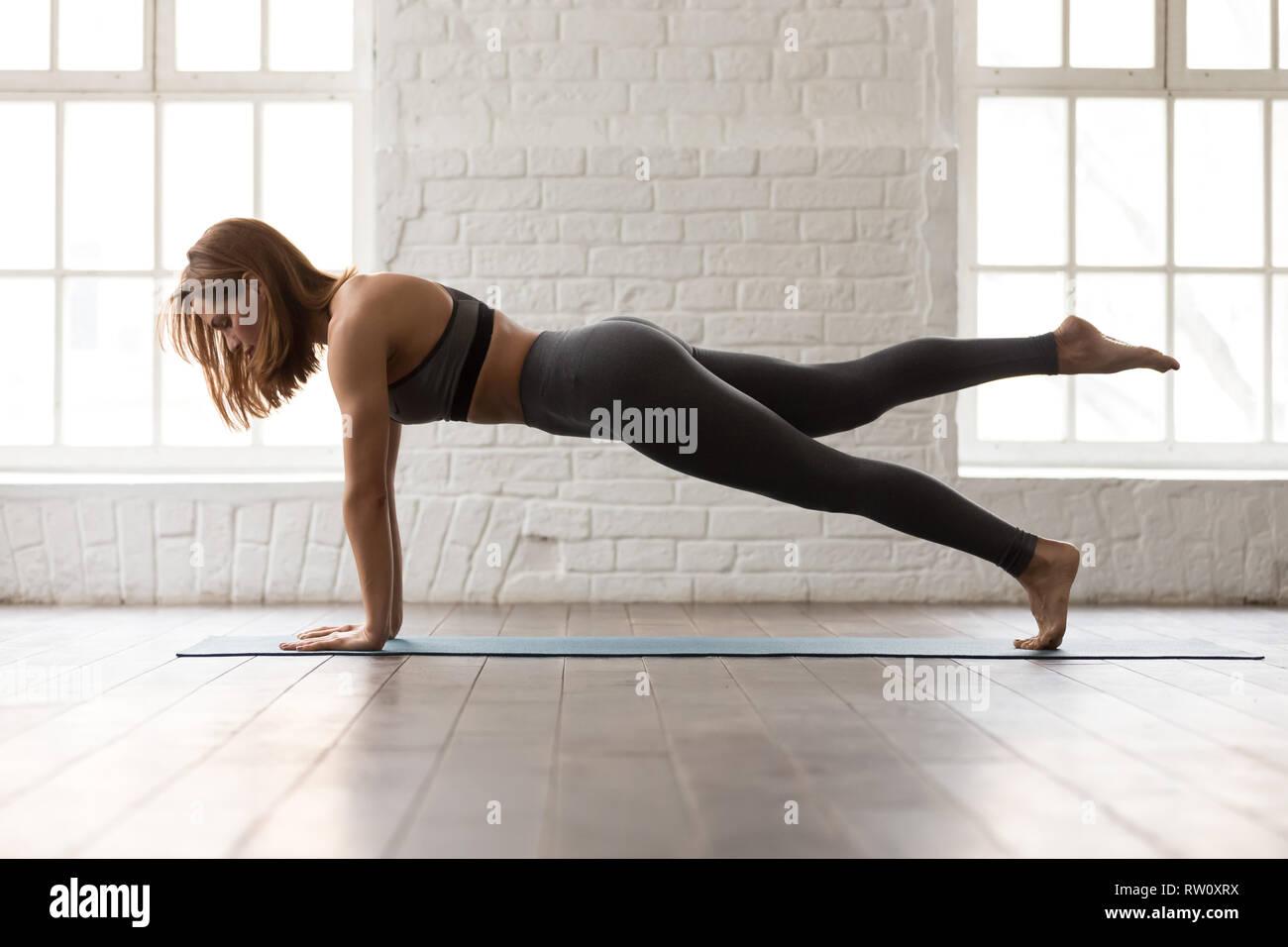 Mujer practicando yoga, empuje ups o sai prensa ejercicio, tablón Foto de stock