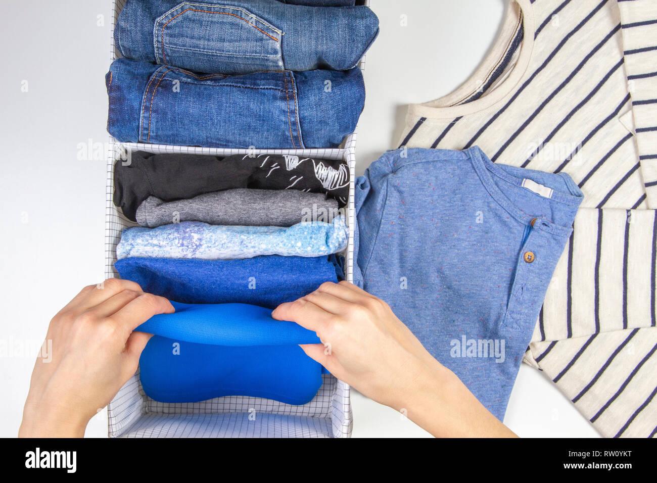 Mujer manos asear la ropa para niños en el canasto. Almacenamiento vertical  de ropa c8cd7a93d61