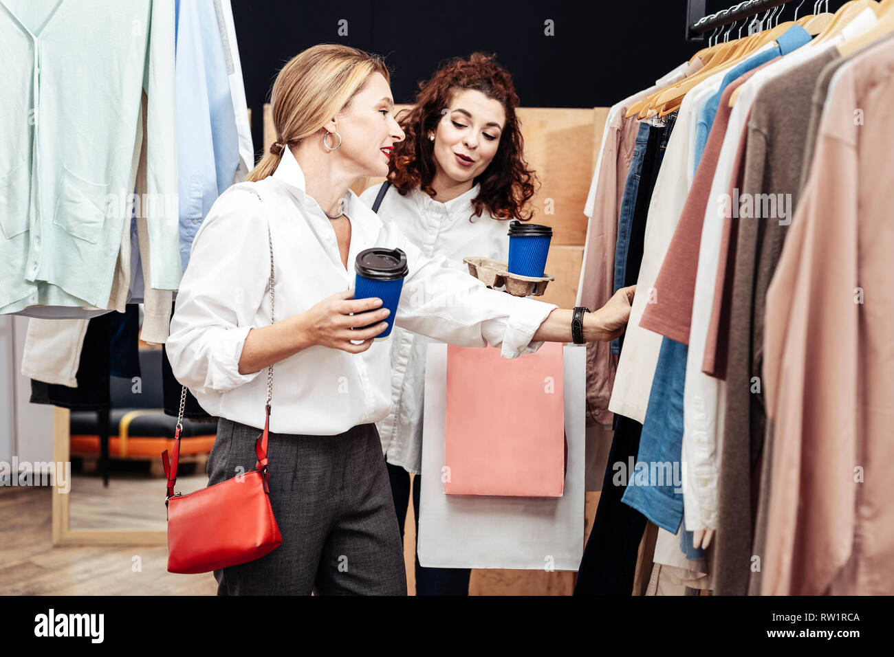 Hija dando consejos para su madre buscando ropa nueva Foto de stock