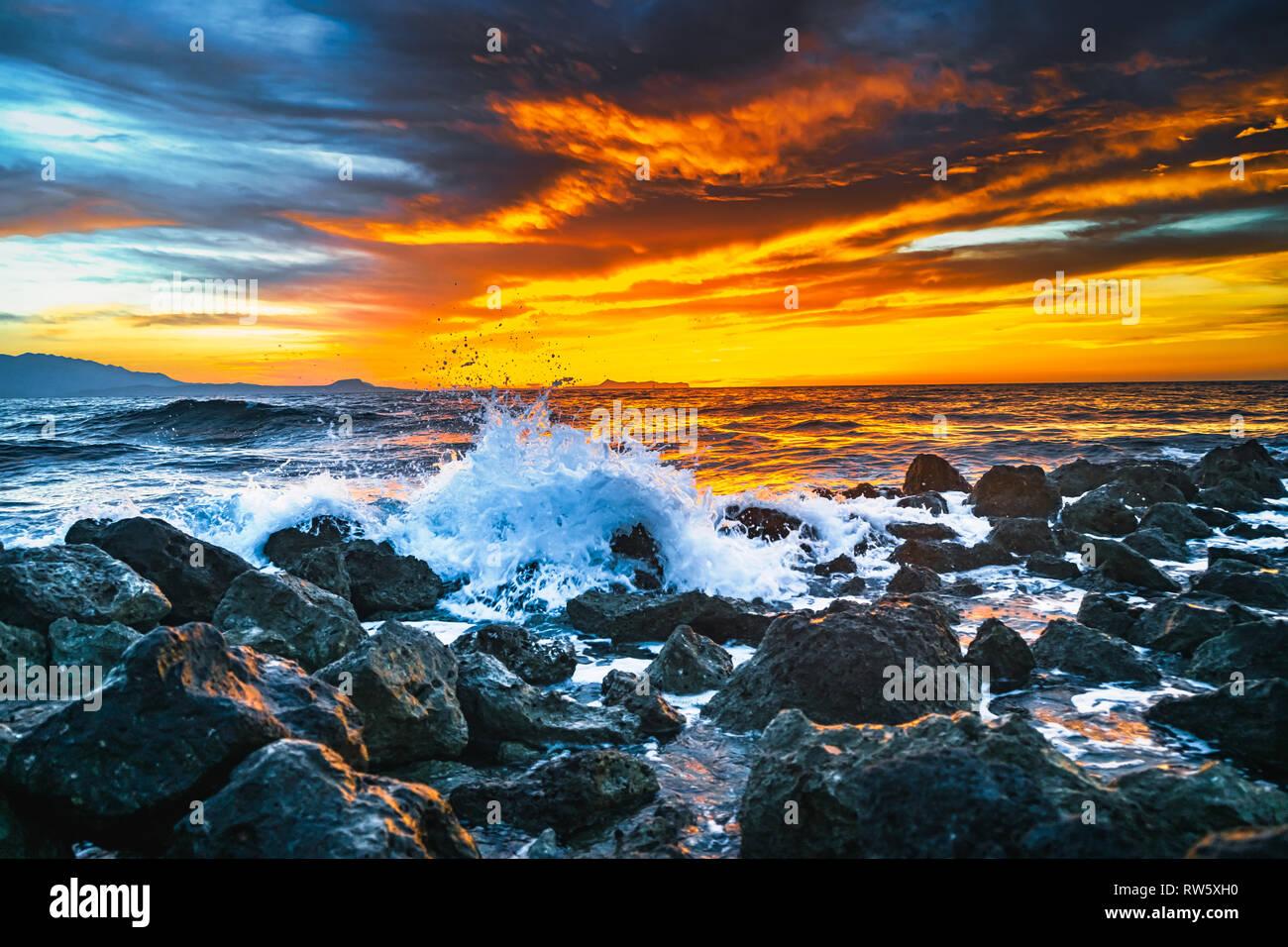 Puesta de sol brillante bajo la tormenta con olas del mar salpica Foto de stock