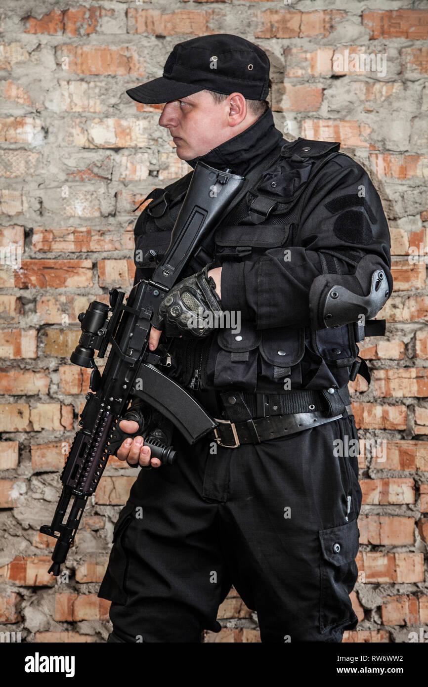 Operador de las fuerzas especiales en uniforme negro y chaleco antibalas. Imagen De Stock