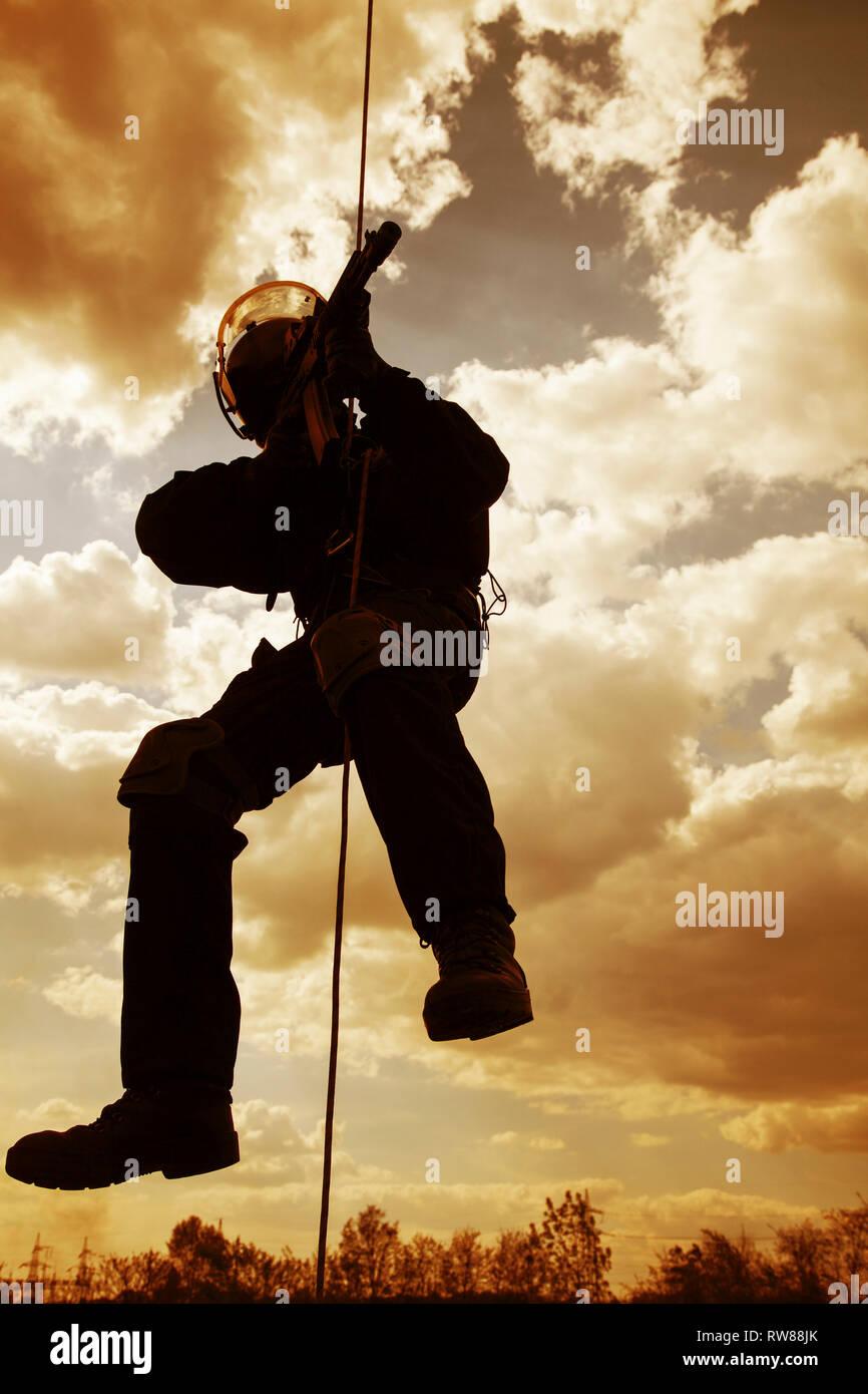 Operador de fuerzas especiales rappel con armas durante un asalto. Imagen De Stock