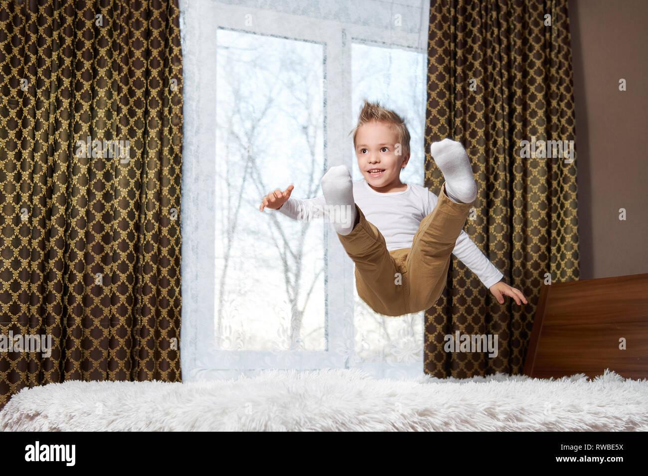 Niño fun home. Niño alegre en movimiento saltando riendo en la cama. Niño de 6 años felizmente juega por la mañana en la sala. Foto de stock
