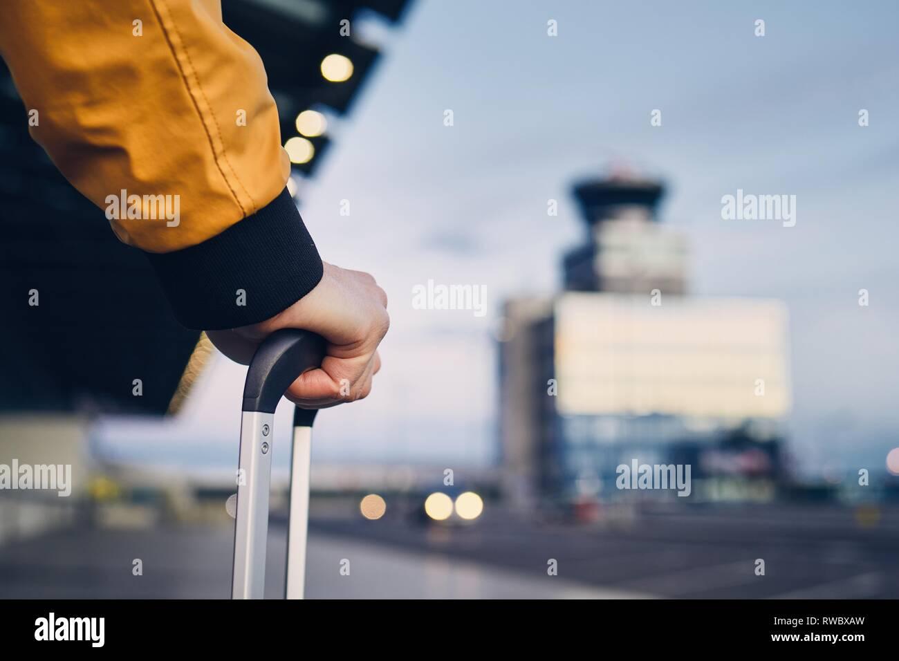Mano del joven hombre sujetando el equipaje contra la terminal del aeropuerto. Foto de stock