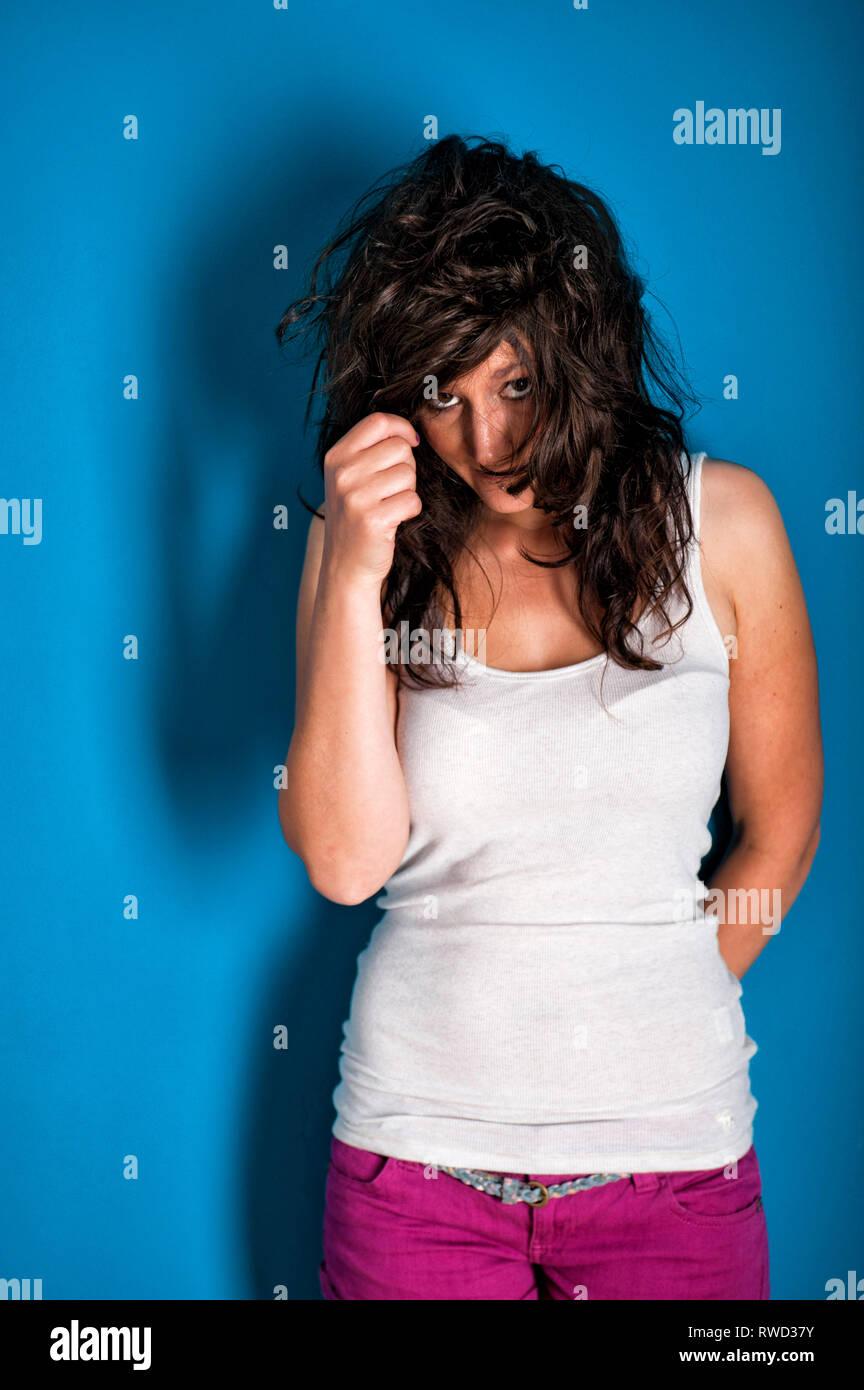 Dunkel haarige Junge Frau mit weissem pinken Hotpants und einer tuerkisen Tanktop steht vor und Wand hat ihre Haare ins Gesicht caído lassen. Sie sch Foto de stock