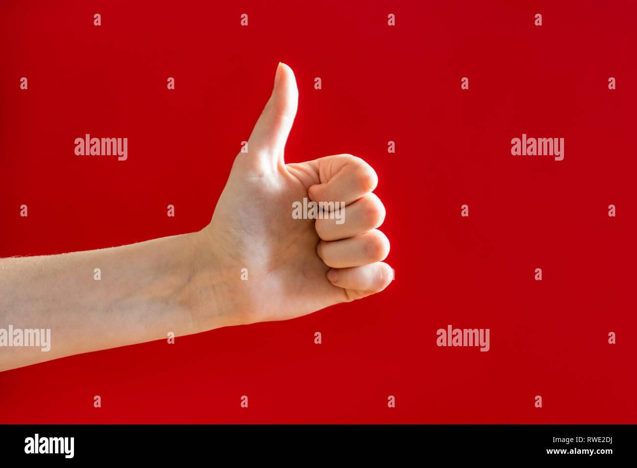 """Thumbs up, gesto de aprobación de concepto. Mano mostrando un """"pulgar arriba"""" signo en vibrante fondo rojo Imagen De Stock"""