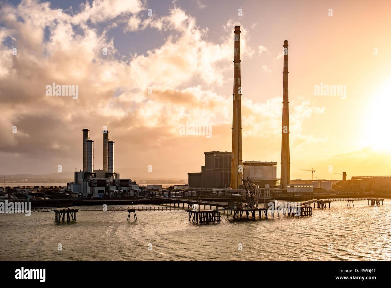 Dublín / IRLANDA - Marzo 03 de 2019: Poolbeg Power Station en el puerto produciendo durante la puesta de sol. Foto de stock