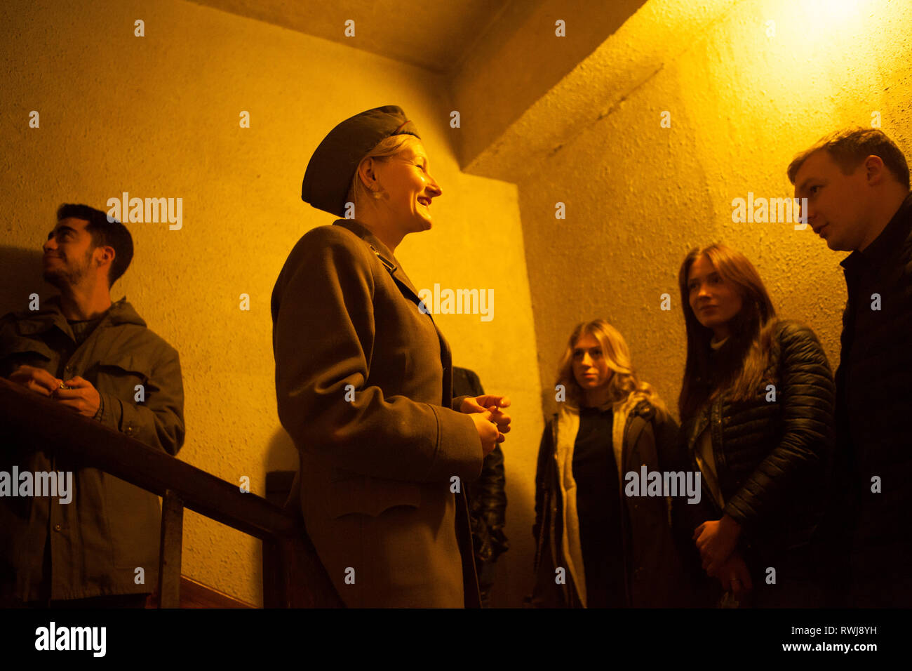 Turistas y guía de mujeres en uniforme militar sobre la escalera en la guerra fría, el búnker Ligatne, Letonia Imagen De Stock