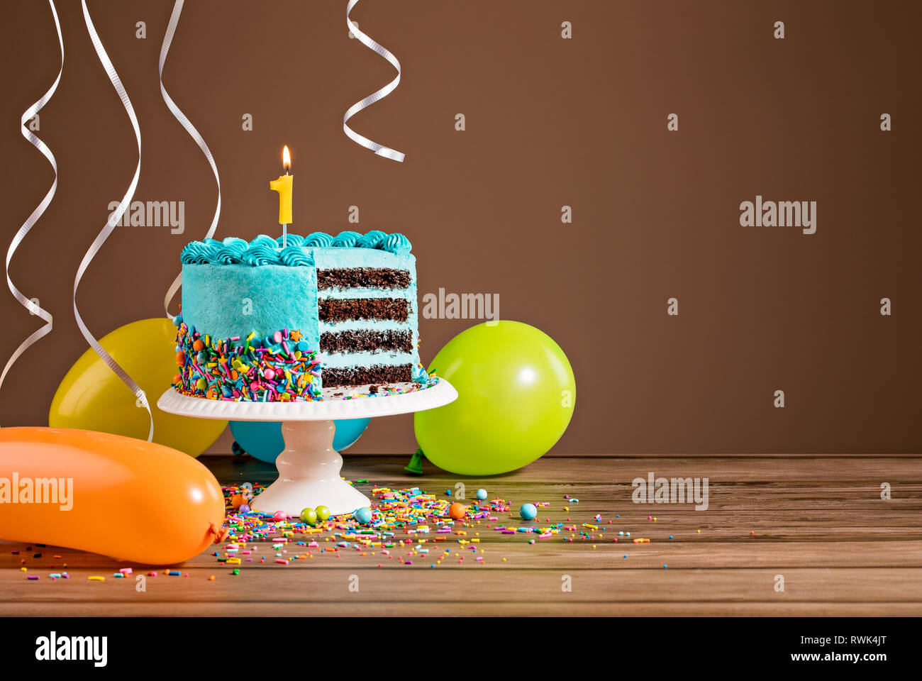 Tarta de Cumpleaños con buttercream azul hielo y globos de colores y una vela número 1. Imagen De Stock