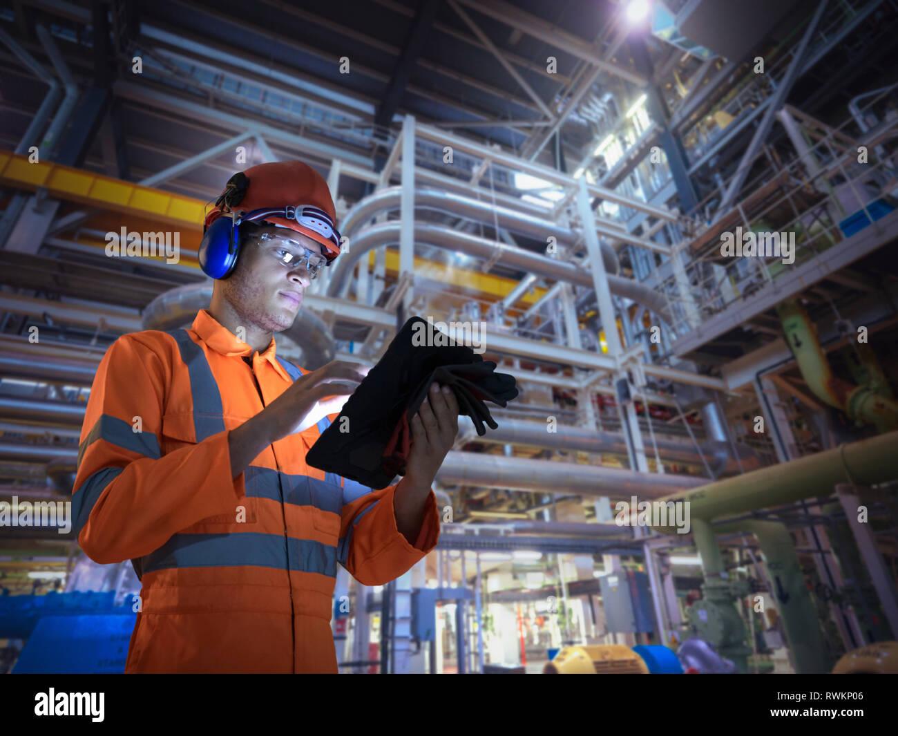Imagen compuesta de ingeniero en la estación de energía nuclear mediante tableta digital Foto de stock