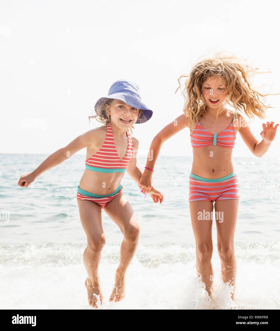 Dos hermanas en la adecuación de los bikinis chapoteando en el mar, Portoferraio, Toscana, Italia Imagen De Stock
