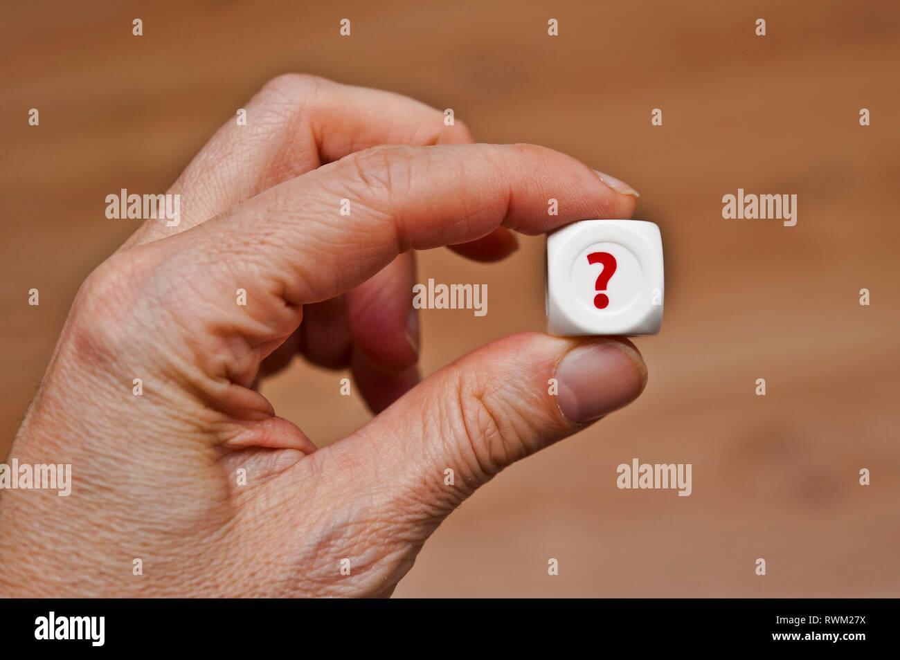 Mano sujetando un morir con signo de interrogación Imagen De Stock