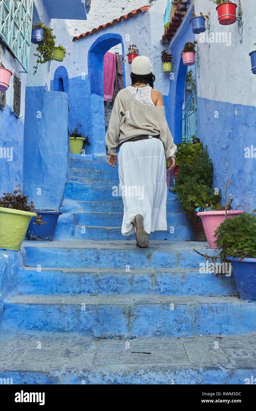 Vista posterior de la dama en la falda y sombrero azul subiendo escaleras cerca de casas antiguas en Marrakech, Marruecos Foto de stock