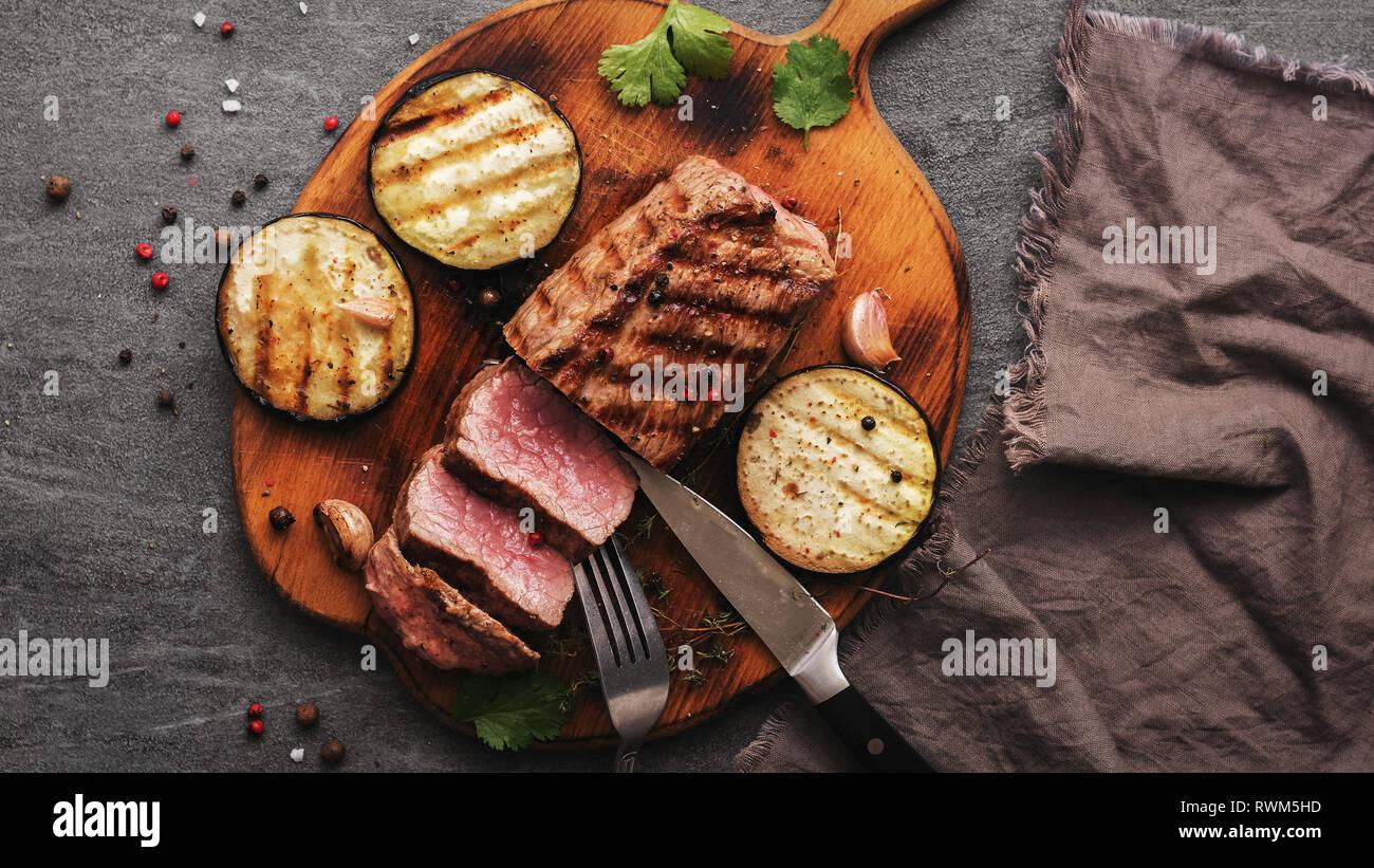 Filete de ternera bistec medio raro con hortalizas y especias sobre una tabla para cortar en rodajas. Vista desde arriba Foto de stock