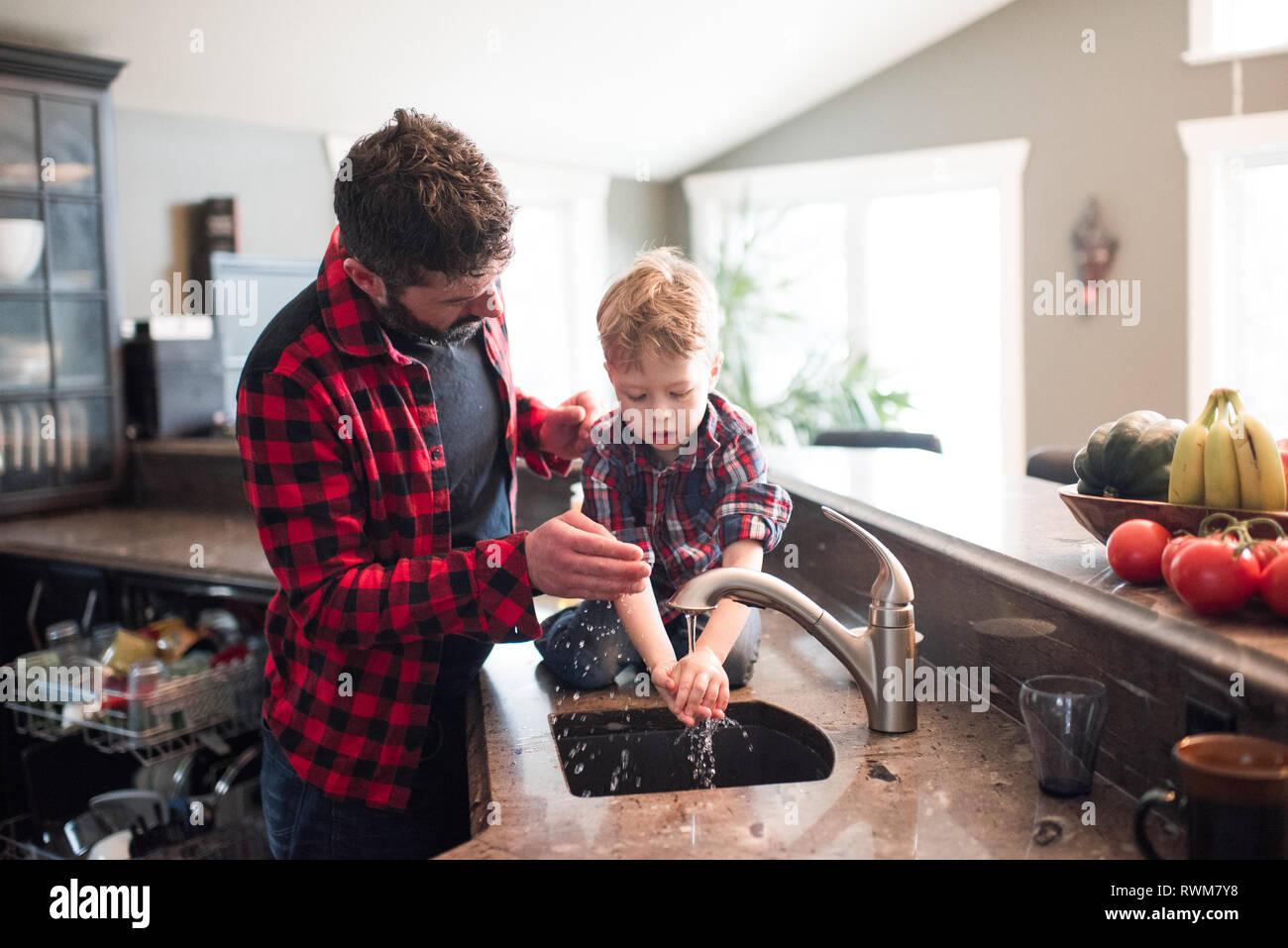 Padre Mira hijo lavarse las manos en el lavabo de la cocina Foto de stock