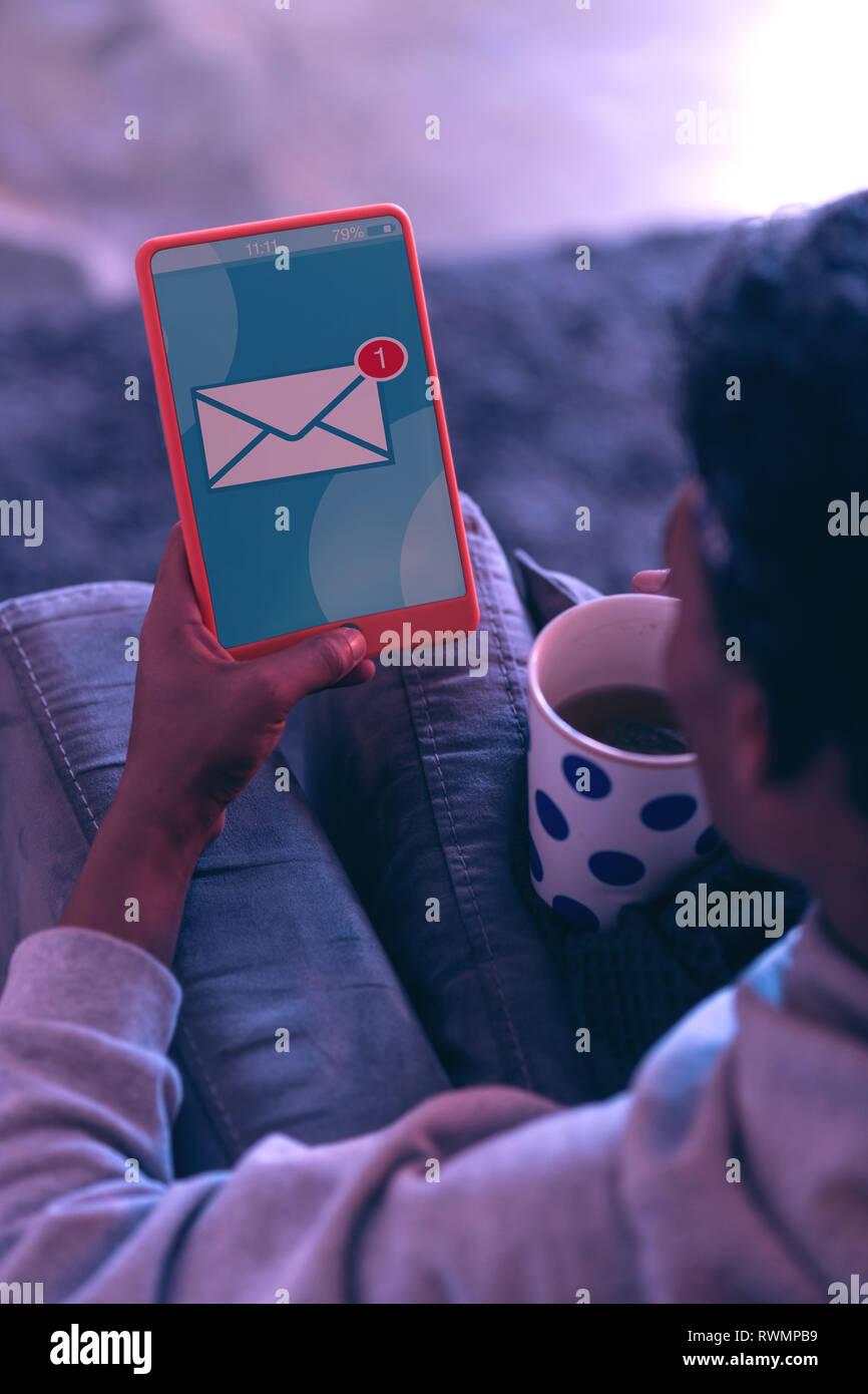 Mientras joven beber té, recibiendo el mensaje sobre la tableta. Foto de stock